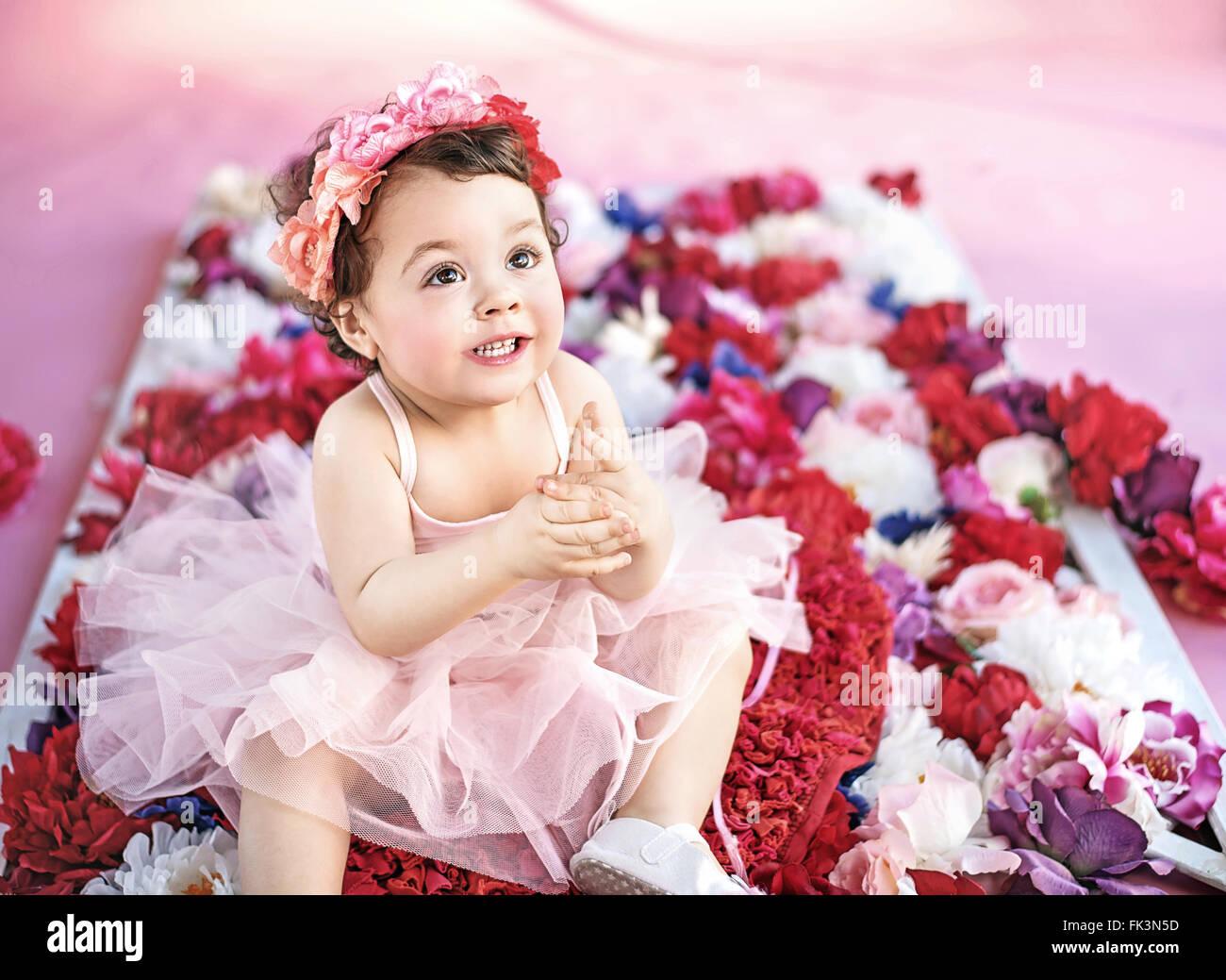 Carino ragazza seduta su un mazzo di fiori Immagini Stock