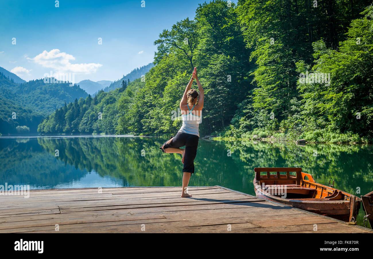 Esercizi yoga a foreste di montagna lago. Immagini Stock
