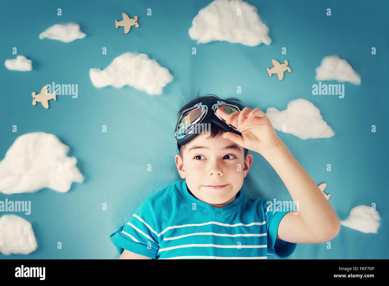 Ragazzo disteso sulla coperta con il bianco delle nuvole Immagini Stock
