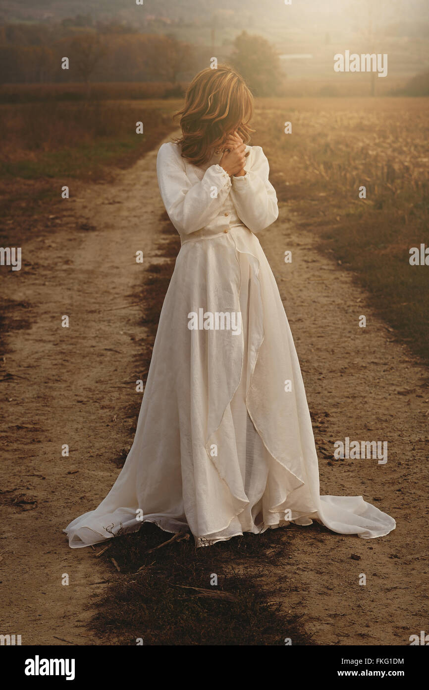 Lone donna con vintage abito da sposa in campagna . La purezza e l'innocenza Immagini Stock
