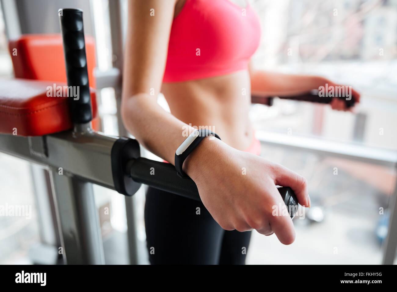 Attraente donna giovane atleta con tracker di fitness su mano lavorando in palestra Immagini Stock