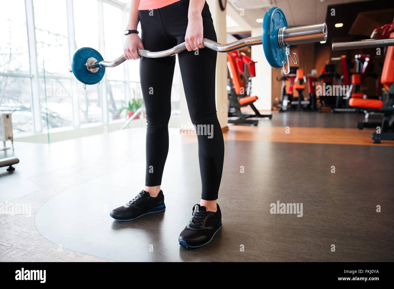 Primo piano di gambe di donna giovane atleta e permanente di esercizio con barbell in palestra Foto Stock