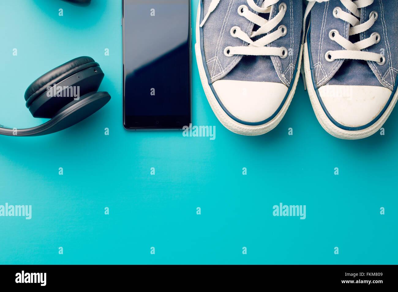 Cuffie, smart phone e sneakers su sfondo colorato Immagini Stock