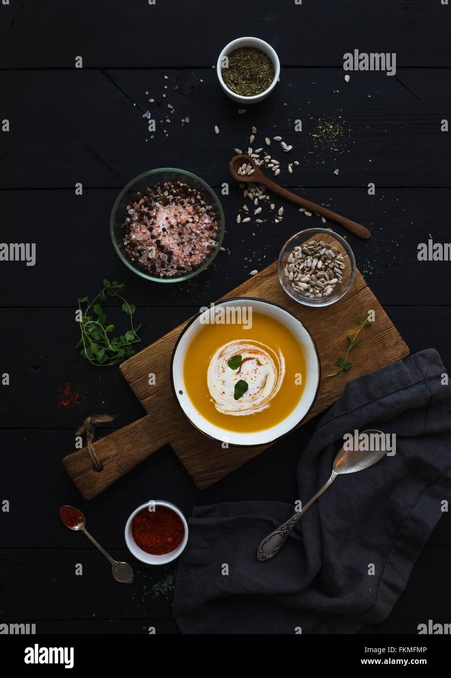 Zuppa di zucca con panna, semi e spezie in stile rustico recipiente di metallo sulla tavola di legno su grunge sfondo Immagini Stock