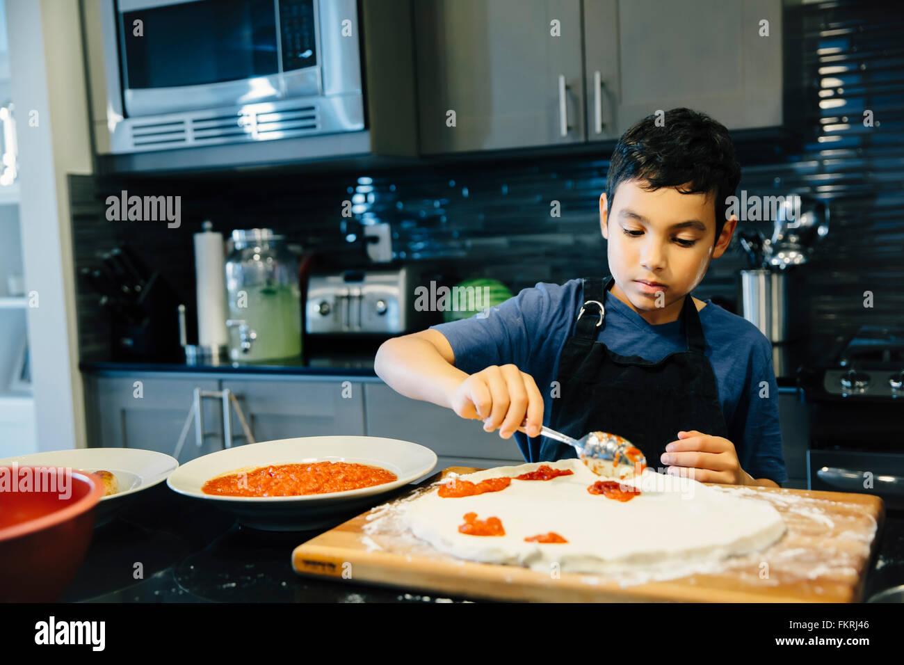 Razza mista boy rendendo la pizza in cucina Foto Stock