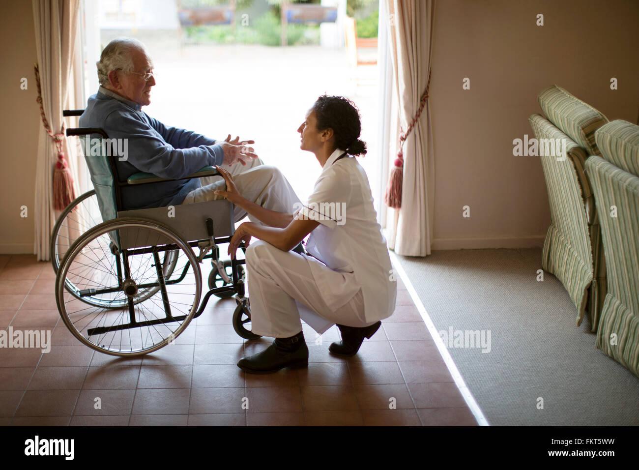 L'infermiera di parlare al paziente in sedia a rotelle Foto Stock