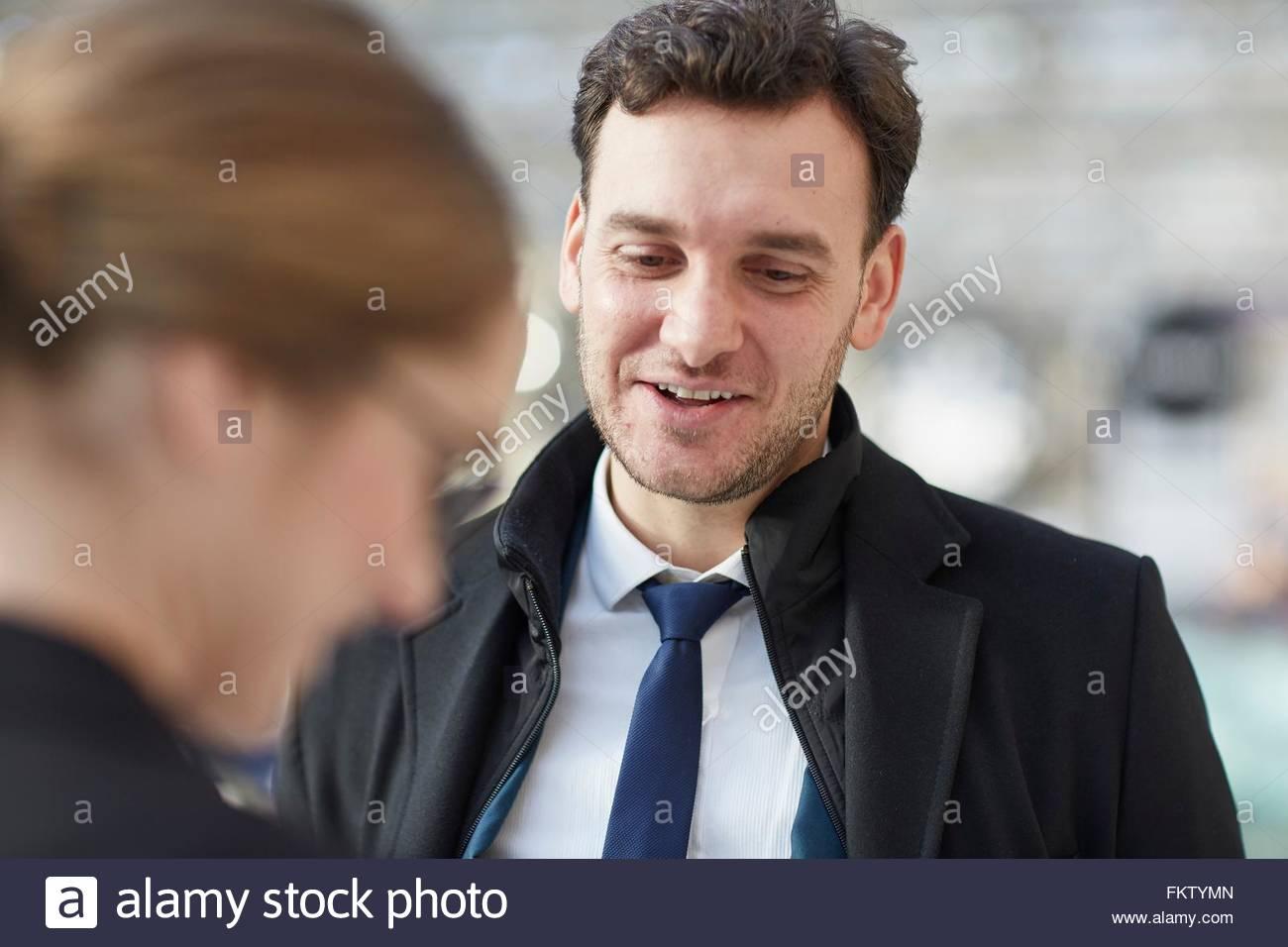Business man parlando a un collega guardando giù sorridente Immagini Stock