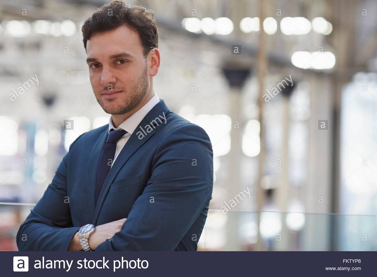 Imprenditore indossare tuta, braccia incrociate guardando sorridente della fotocamera Immagini Stock