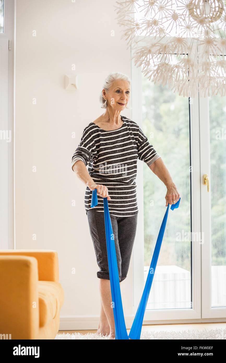 Senior donna che esercitano nel soggiorno tirando la banda di resistenza Immagini Stock