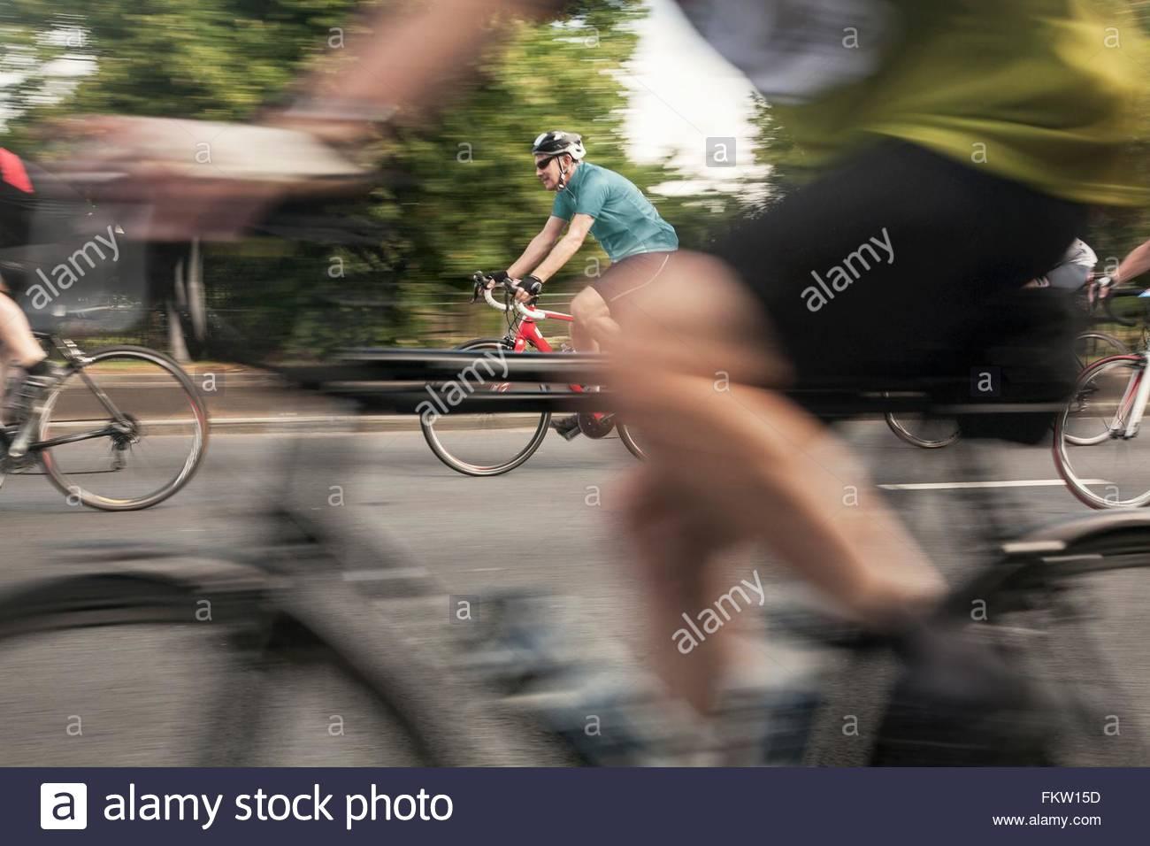 Close up dei corridori ciclisti accelerando sulla strada urbana nel racing cycle race Immagini Stock