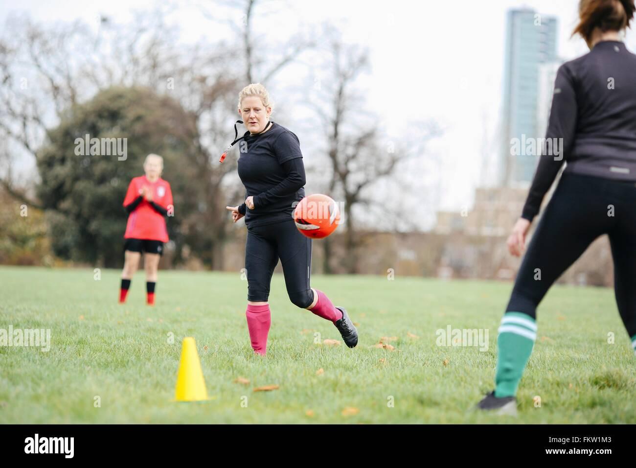 Femmina di giocatori di calcio avente la pratica del calcio in posizione di parcheggio Immagini Stock