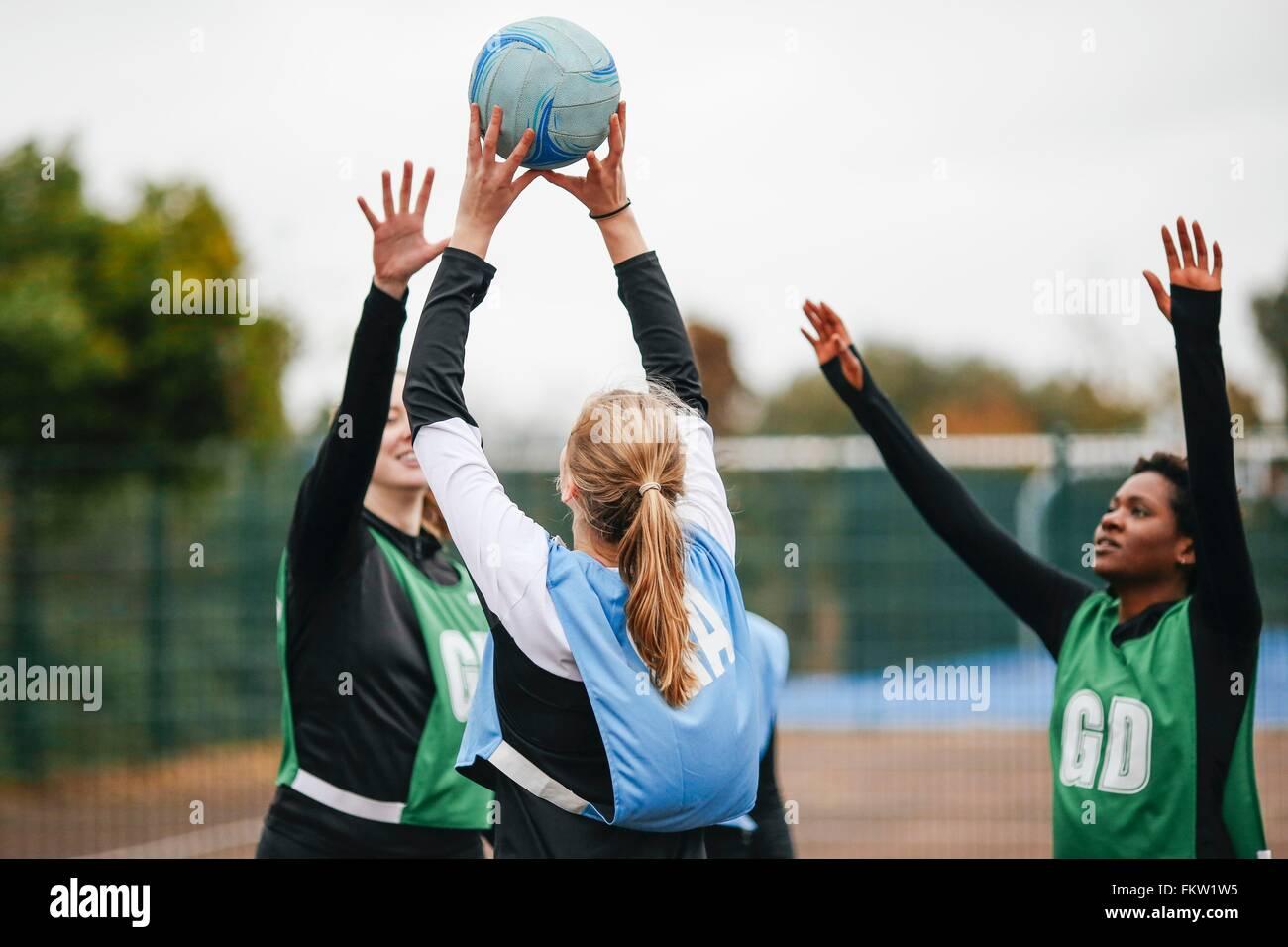 Femmina team netball gettando sulla sfera di netball corte Immagini Stock