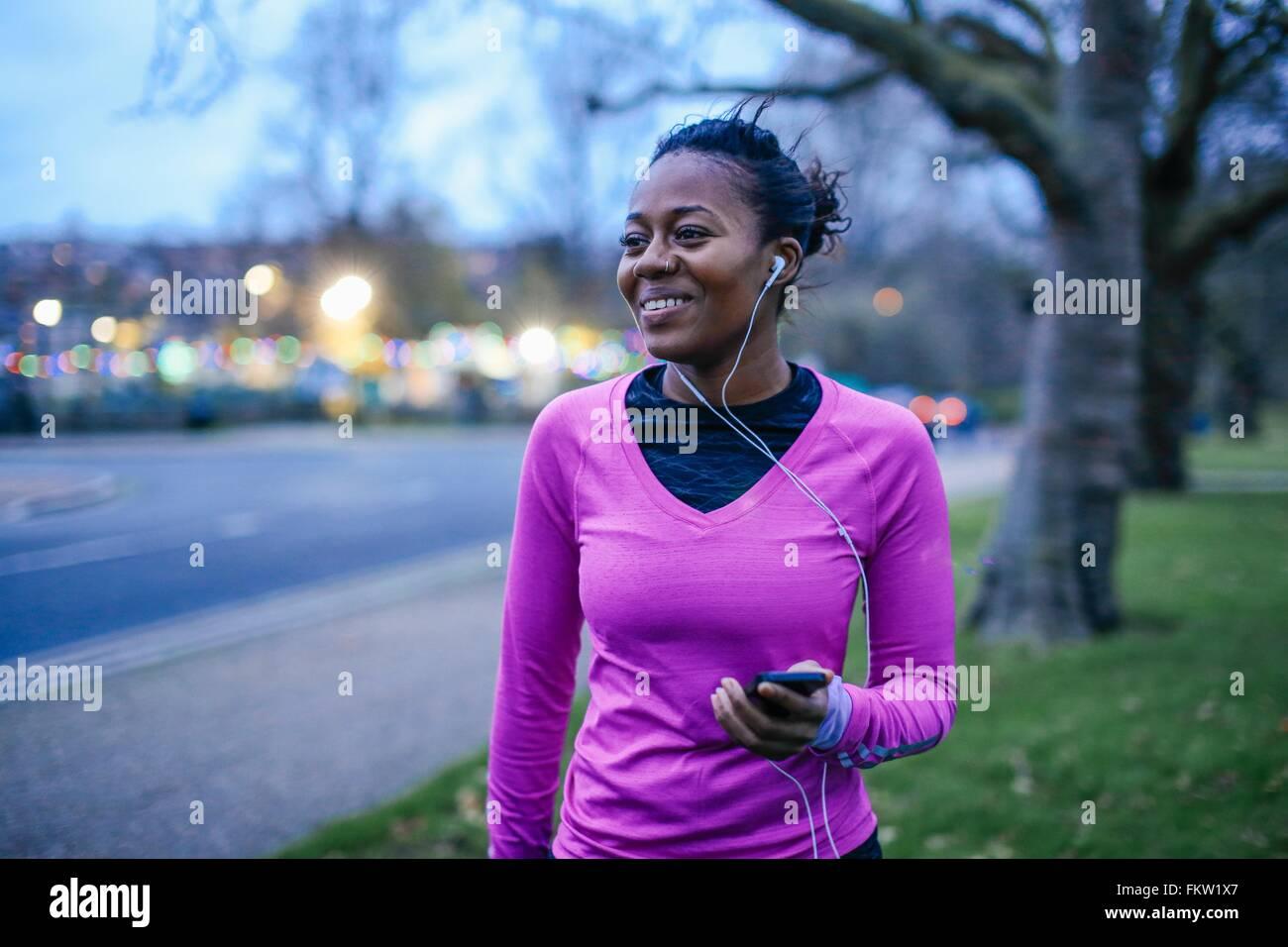 Giovane donna in esercizio i vestiti, indossa gli auricolari Immagini Stock