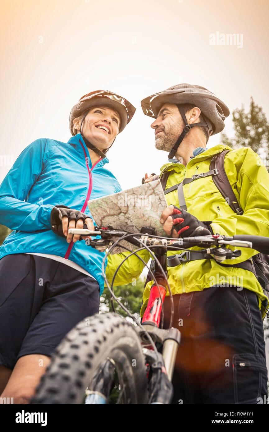 Basso angolo vista della coppia mountain bike giovane con mappa Immagini Stock