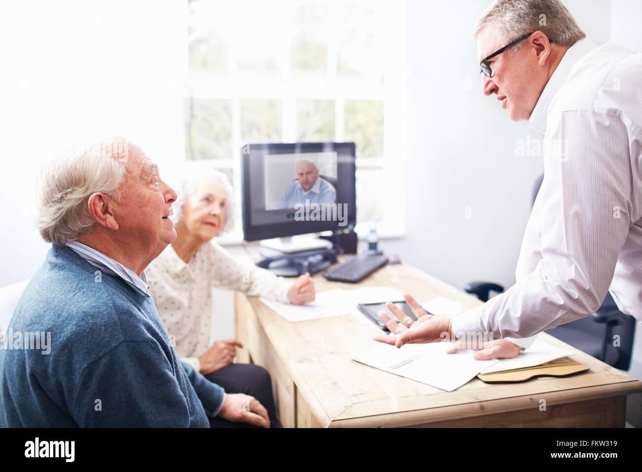 Business man in ufficio avente la discussione con coppia senior Immagini Stock