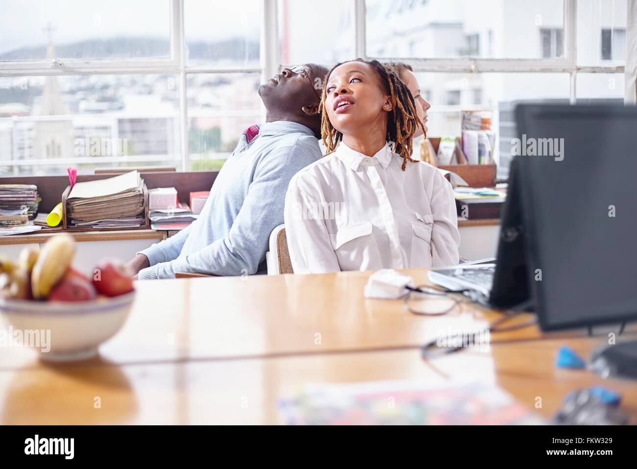 I colleghi di team building task seduta di schiena guardando lontano Immagini Stock