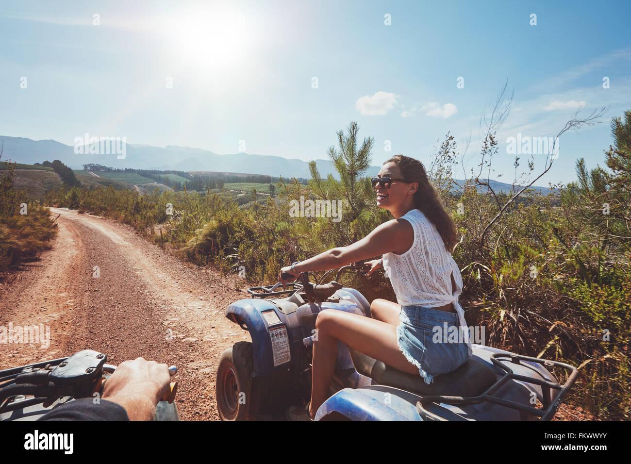 Giovane donna su quad bike su un sentiero. Giovane donna alla guida di veicolo fuoristrada in natura in una giornata Immagini Stock