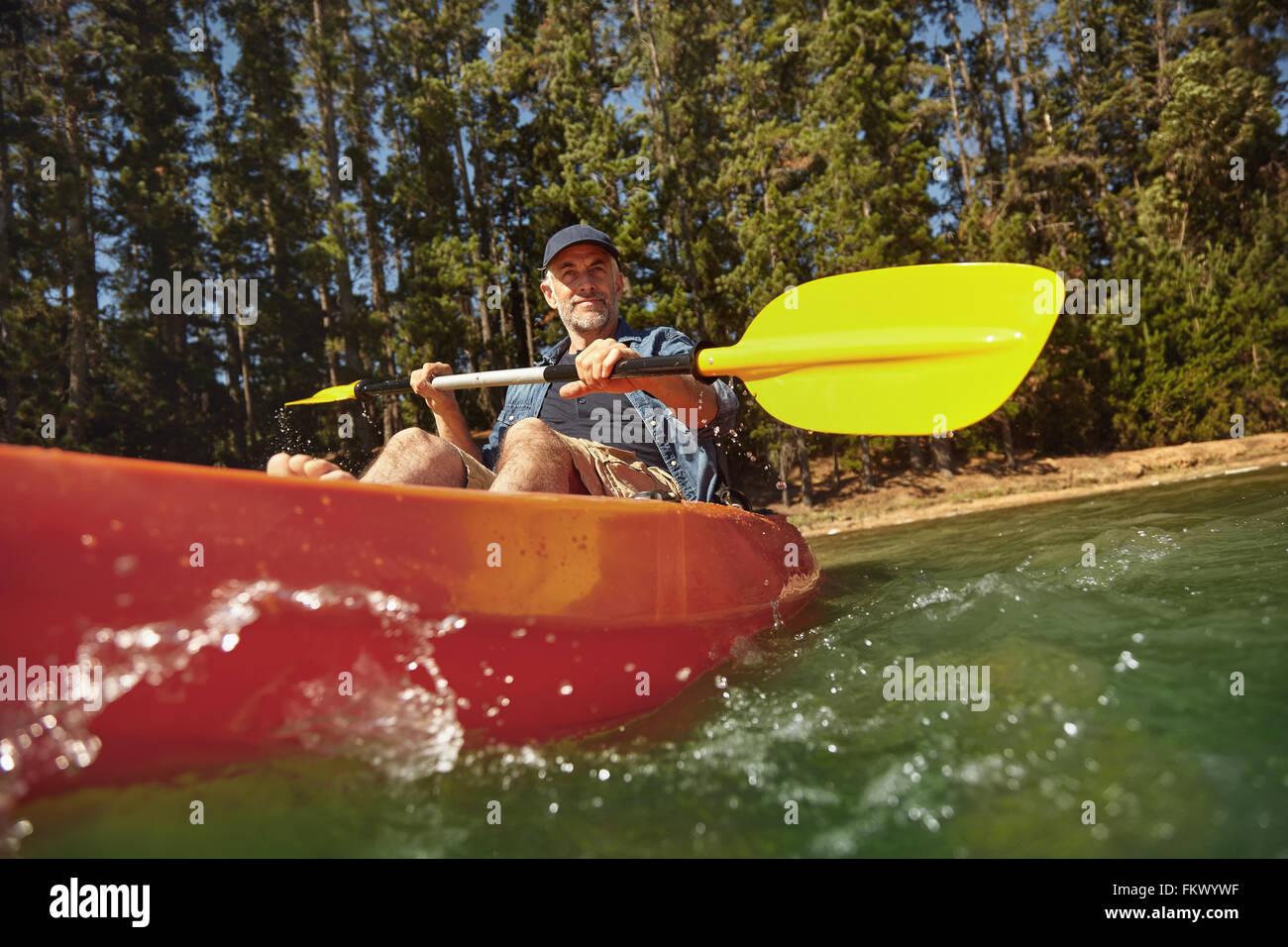 Senior uomo caucasico pagaiando in kayak nel lago. Uomo maturo in canoa sul giorno di estate. Immagini Stock