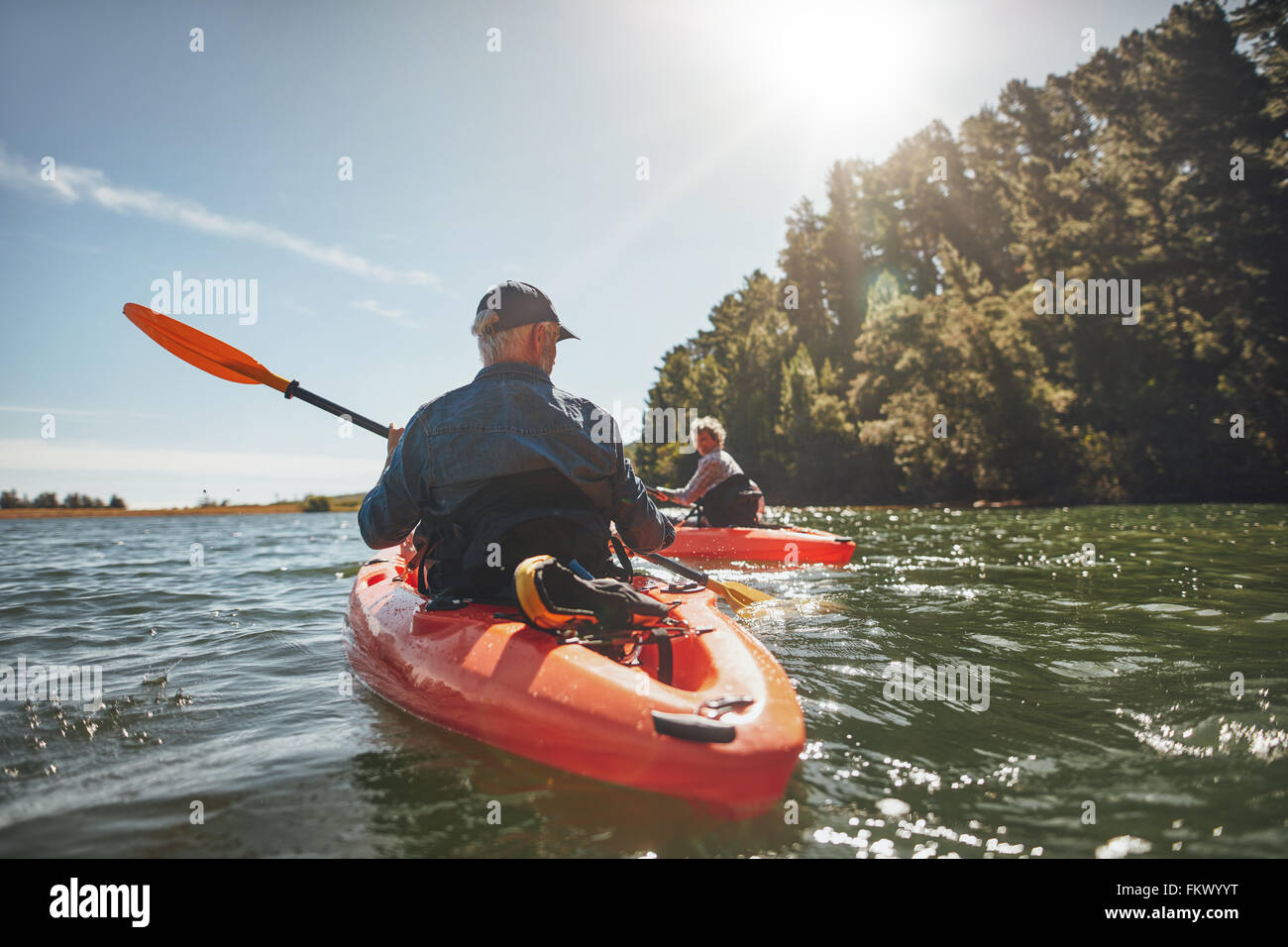 Colpo all'aperto di uomo maturo il canottaggio nel lago con la donna in background. Giovane kayak nel lago in Immagini Stock