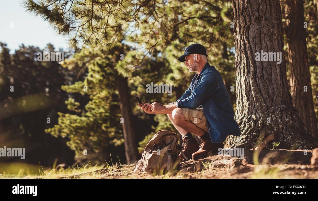 Uomo maturo escursionista seduto da un albero nella foresta e nel controllo della sua posizione utilizzando una Immagini Stock