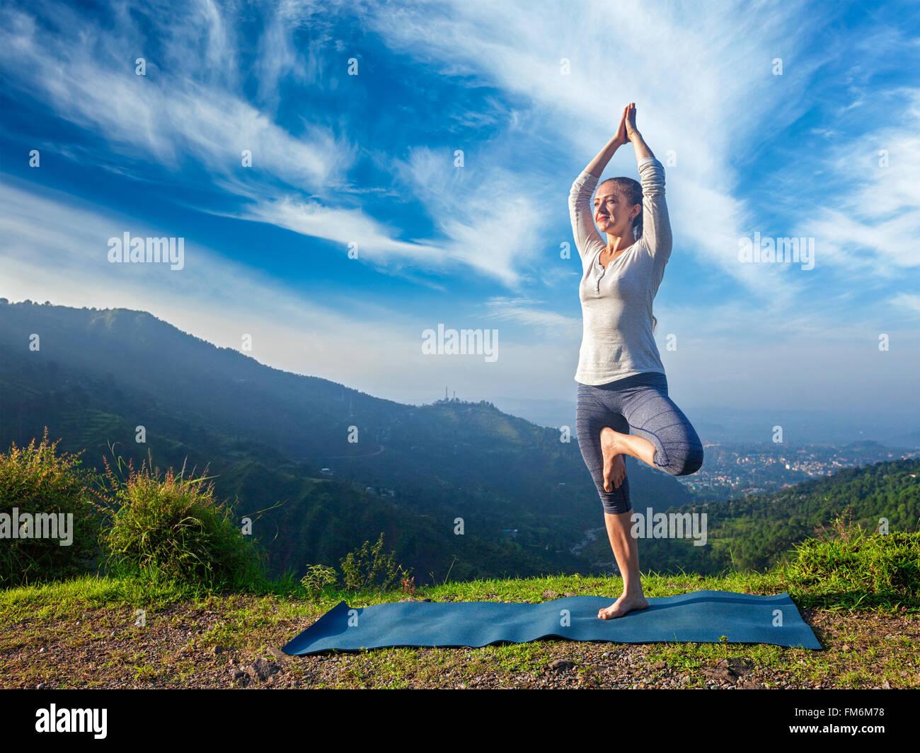 La donna a yoga Vrikshasana tree pongono all'aperto Immagini Stock
