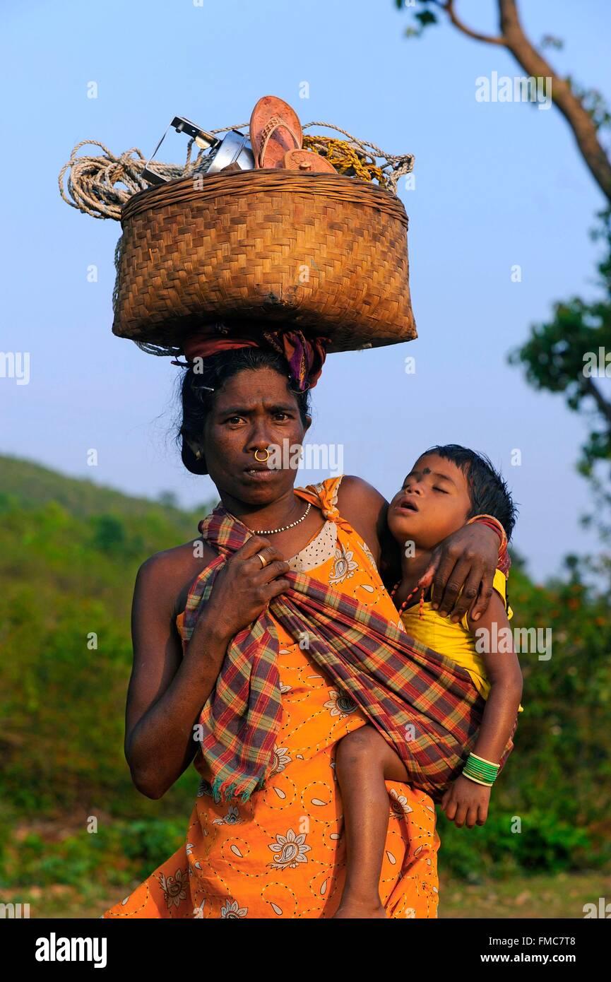 India, Odisha, una donna indiana carichi materiale su una strada di campagna Immagini Stock