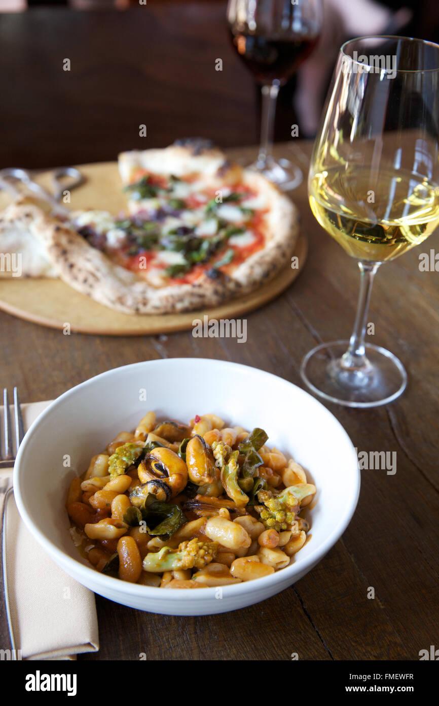 Una scodella di fagioli bianchi, romanesco e zuppa di cozze con vino bianco e una pizza sul tavolo dietro di esso. Foto Stock
