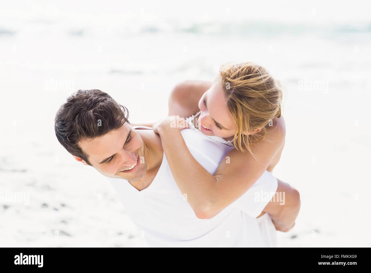 L uomo dando una piggy back per donna sulla spiaggia Immagini Stock