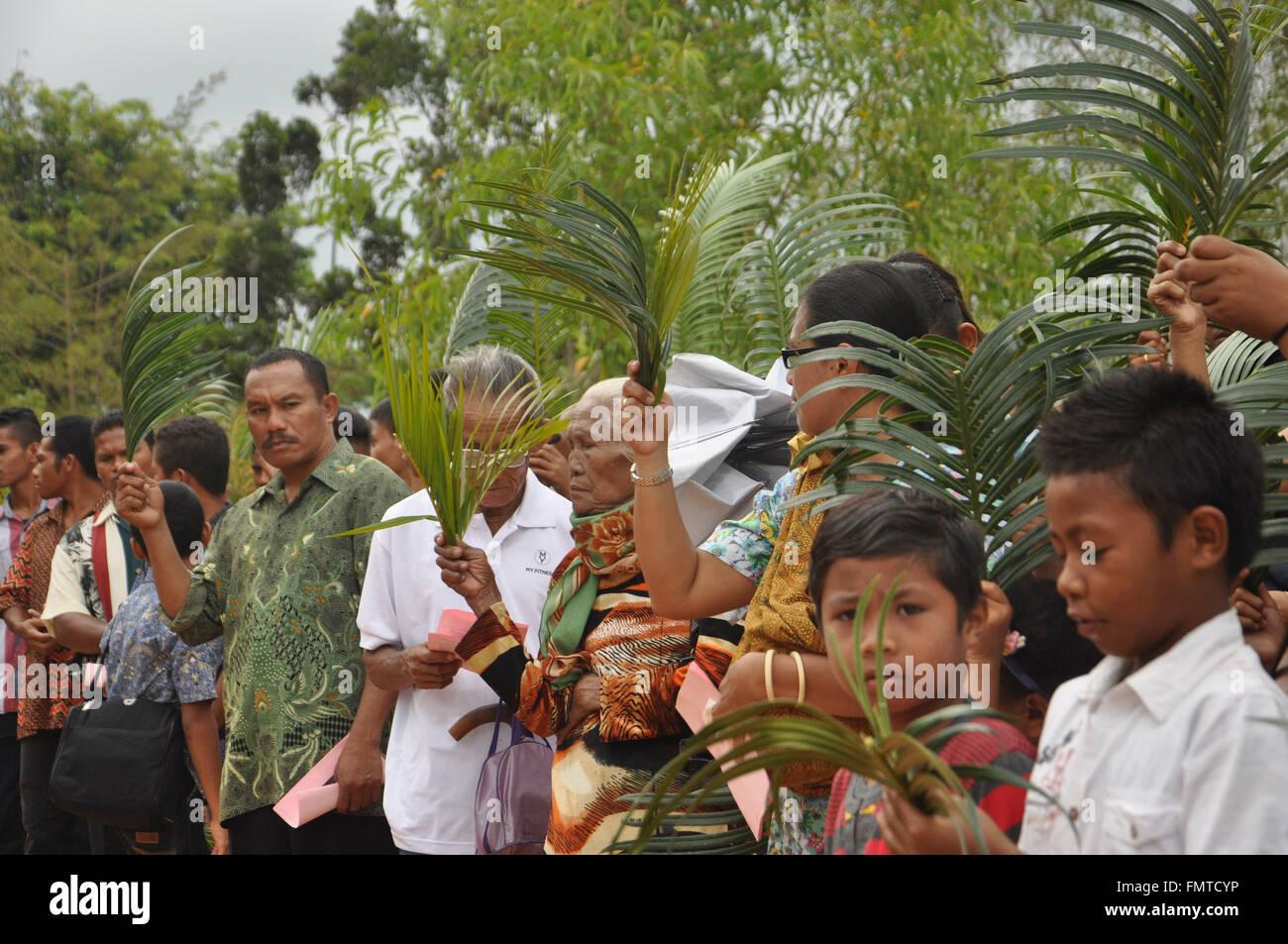 Attendand alzò le loro foglie di palmo di essere benedetta dal parroco durante la Domenica delle Palme a San Immagini Stock