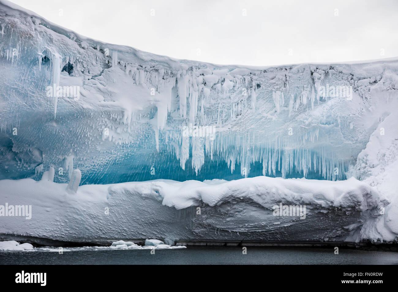 L'Antartide, penisola antartica, isole di pesce, ghiaccioli sulla sporgenza del ghiaccio o grotta Immagini Stock