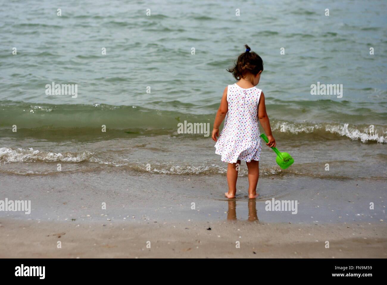 Baby girl permanente sulla spiaggia, Senigallia, Ancona, Marche, Italia Immagini Stock