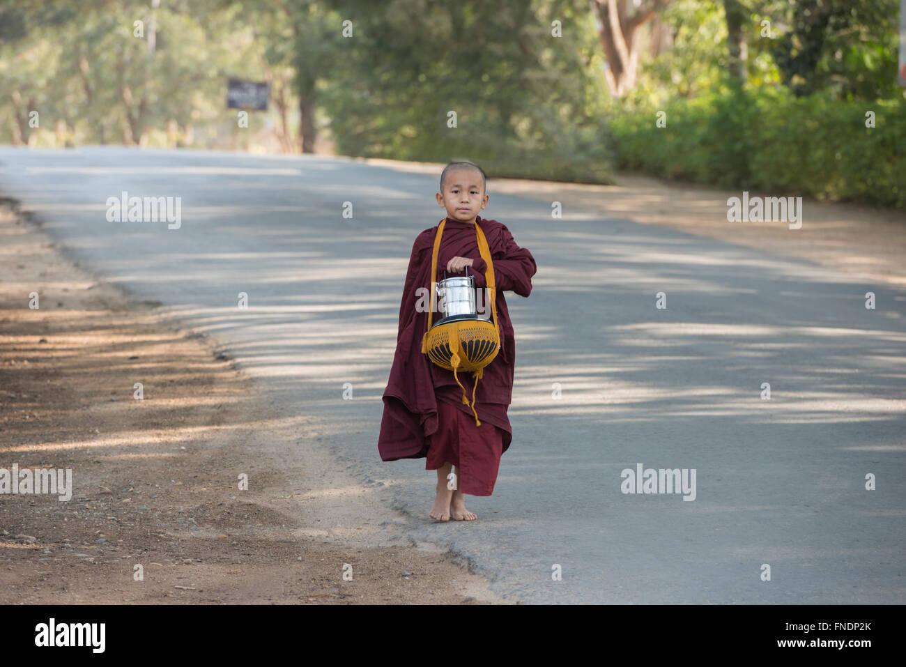 Un giovane monaco sul suo mattina alms round, Bagan, Myanmar Immagini Stock