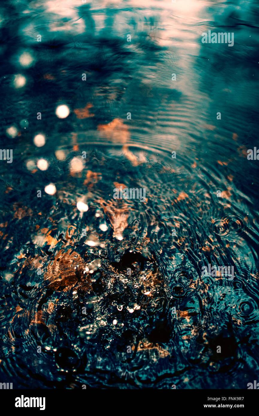 Le goccioline di acqua che rientrano nel fiume Immagini Stock