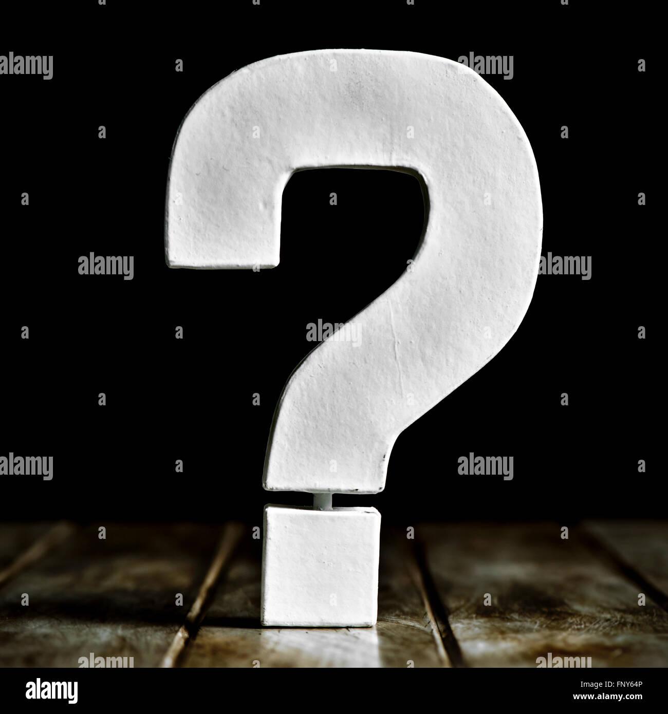 Un bianco tridimensionale di punto interrogativo su un rustico di una superficie di legno contro uno sfondo nero Immagini Stock