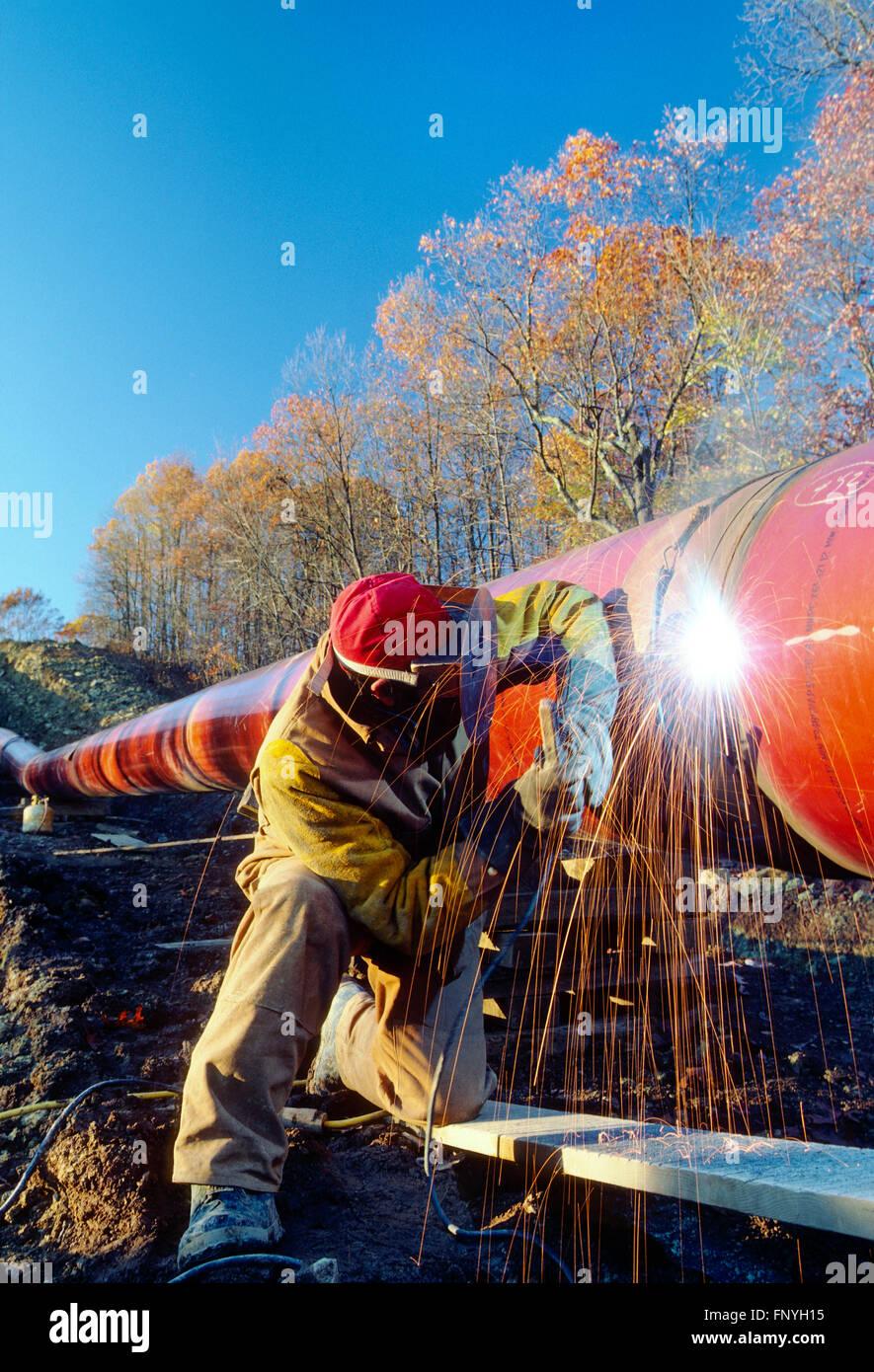 L'uomo la saldatura di una giunzione di pipeline nelle zone rurali del West Virginia; USA Immagini Stock