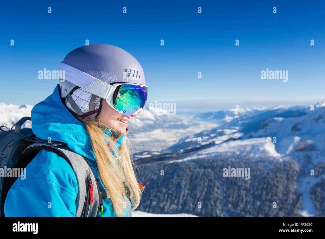 Lo sciatore, con rifiniture con maschere da sci e casco guardando in lontananza, valle Inntal dietro, Axamer Lizum, Immagini Stock
