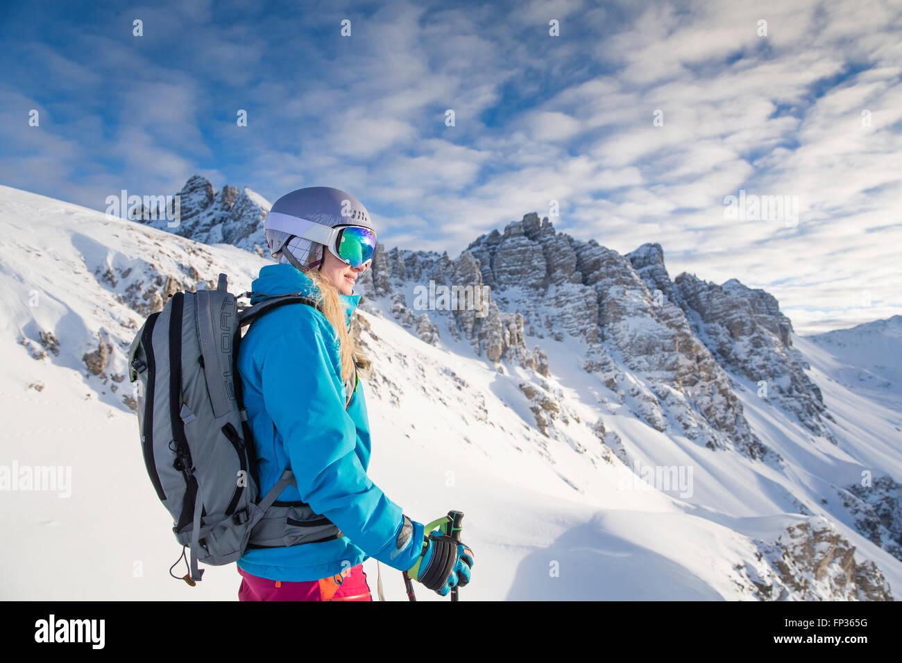 Lo sciatore, con rifiniture con maschere da sci e casco guardando in lontananza, Kalkkögel dietro, Axamer Lizum, Immagini Stock