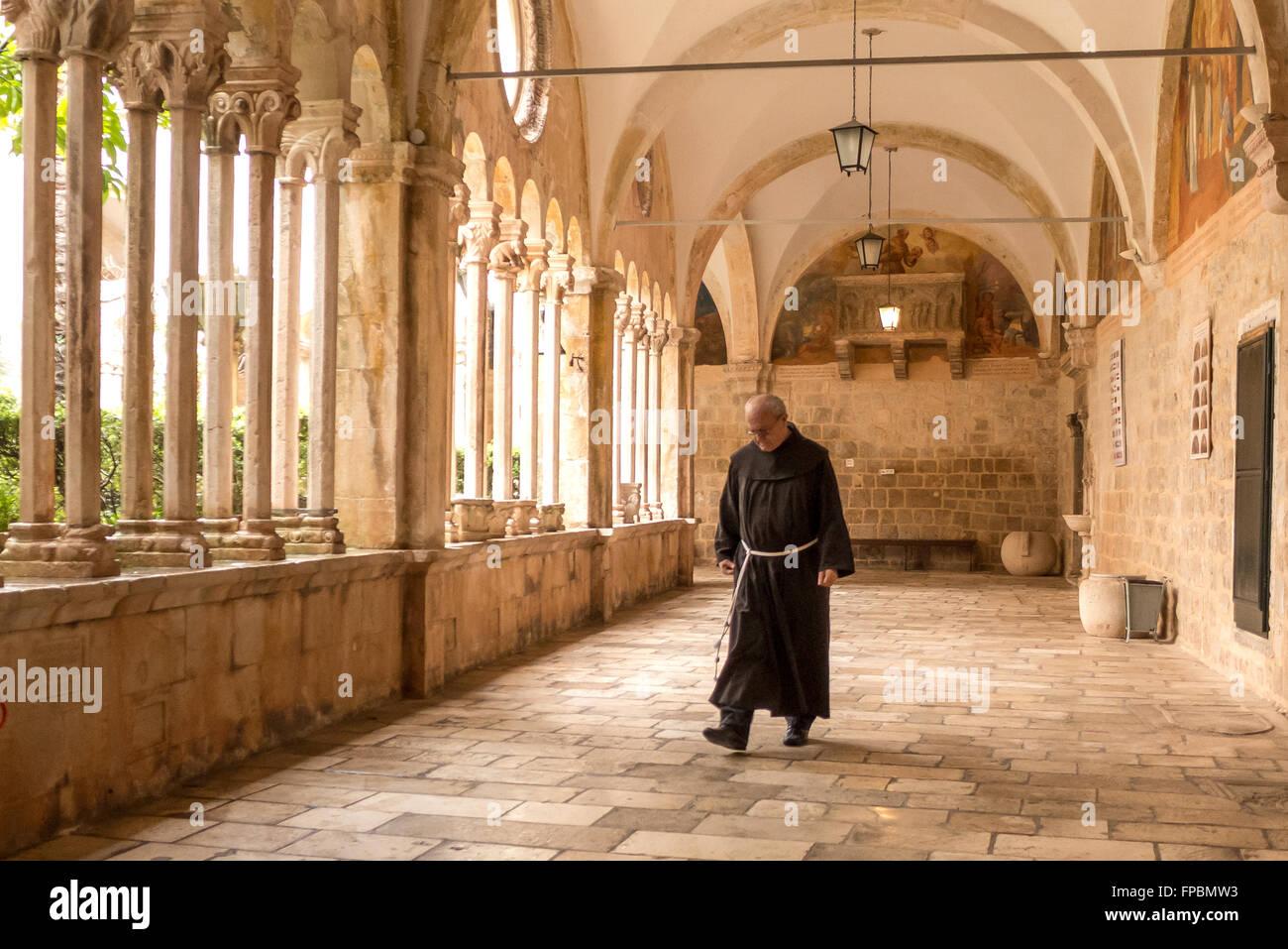 Un monaco all interno del chiostro del convento francescano a Dubrovnik, Croazia. Foto Stock