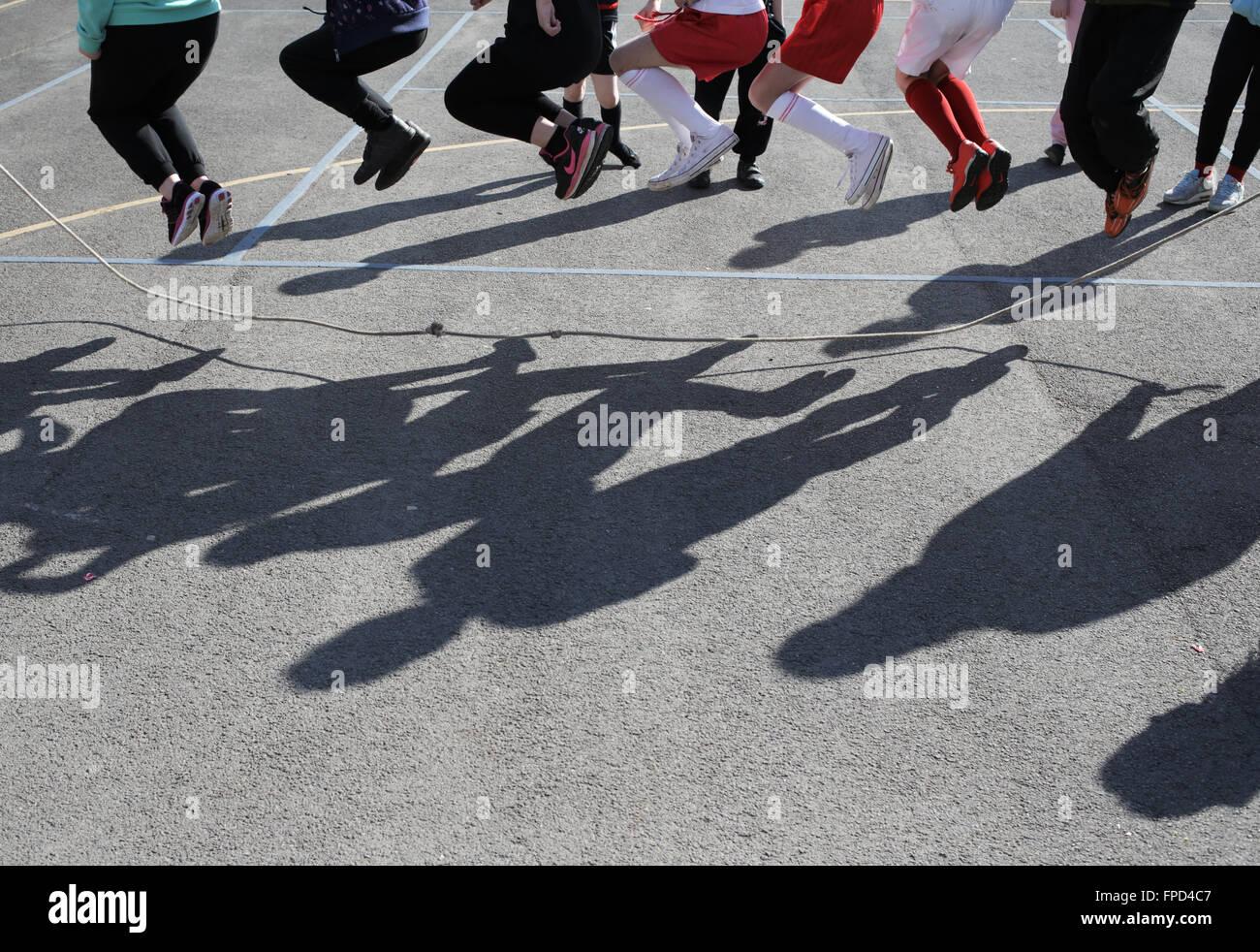 Gli alunni saltando durante la ricreazione in Sala Rossa Junior School in Darlington, County Durham, Regno Unito. Immagini Stock