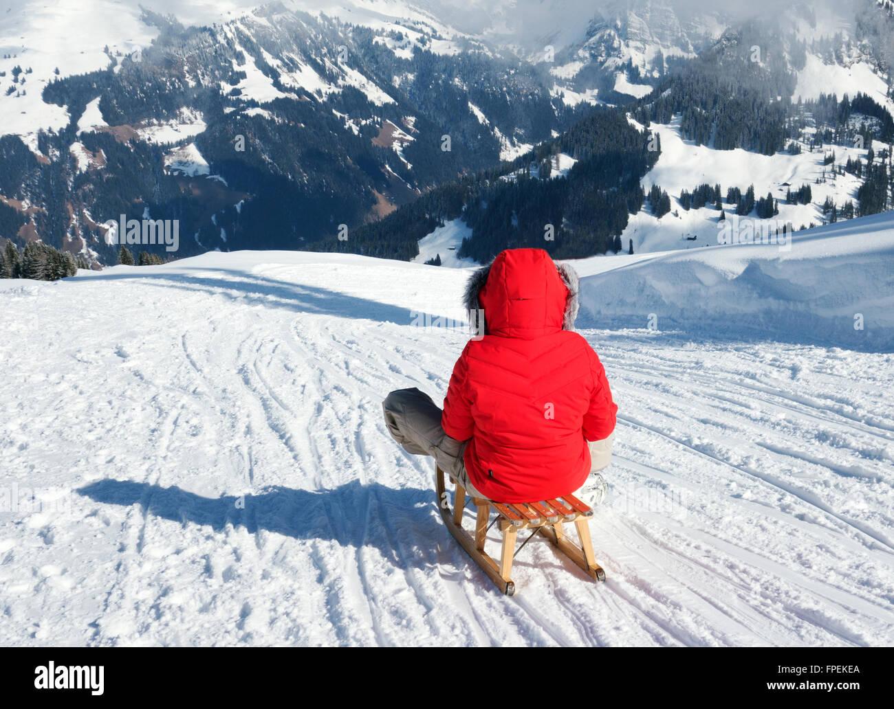 Una giovane donna lo slittino nelle alpi svizzere in vacanza, a Lenk, il Cantone di Berna, Svizzera Europa Immagini Stock