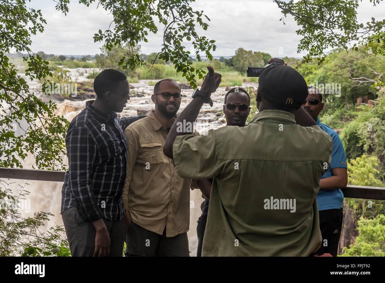 Turisti africani aventi la loro fotografia scattata a Mosi-oa-Tunya National Park, (Victoria Falls), Livingstone, Immagini Stock