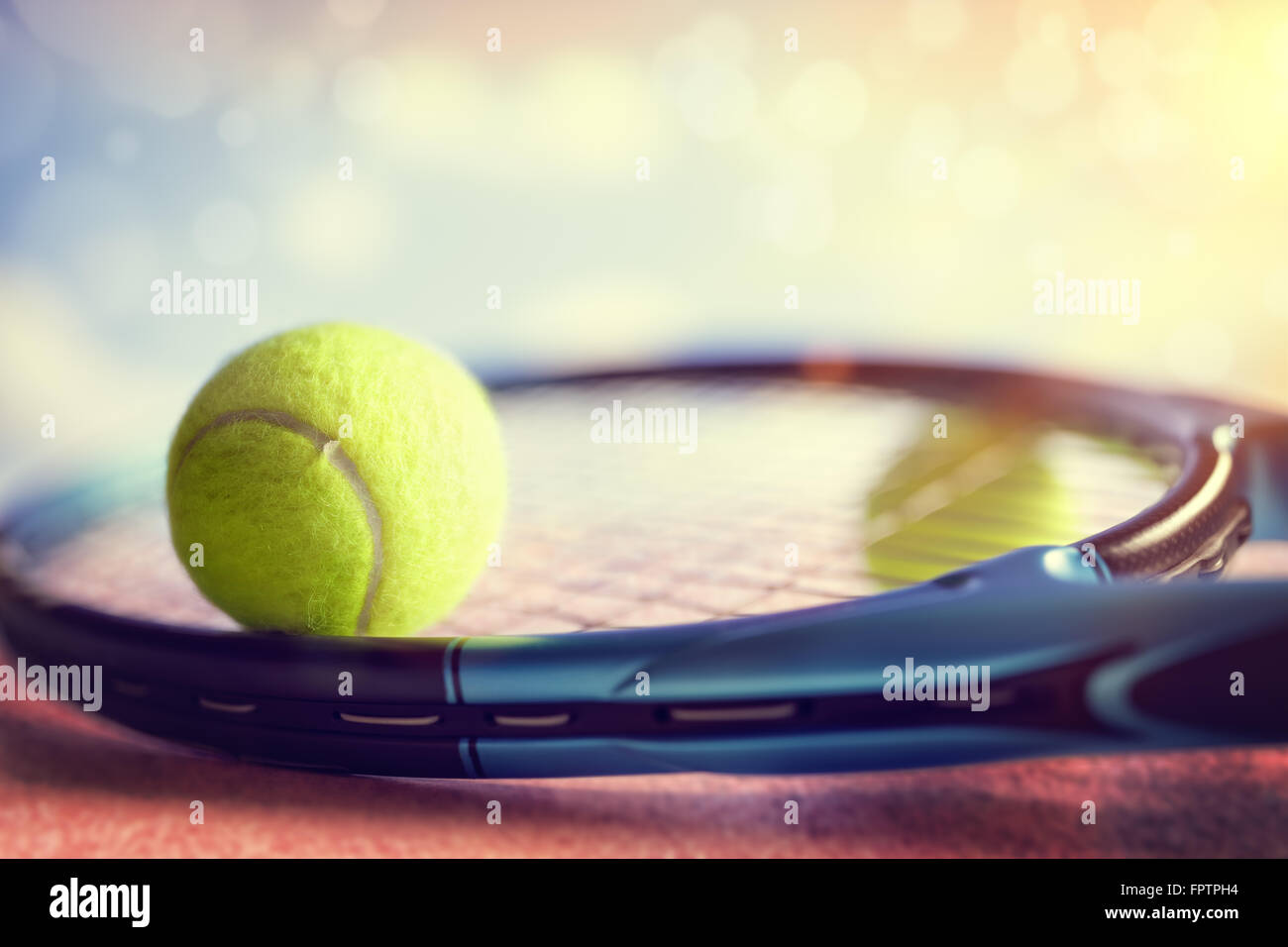 Palla da tennis in appoggio sulla sommità di una racchetta da tennis su un asfalto rosso corte Immagini Stock