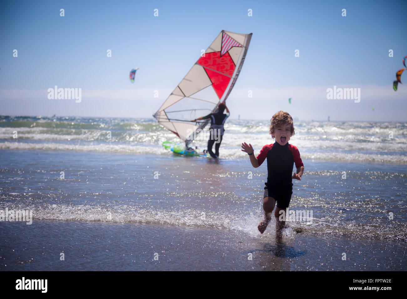 Piccolo bambino correre sulla spiaggia e padre in background di Viana do Castelo, Regione Norte, Portogallo Immagini Stock