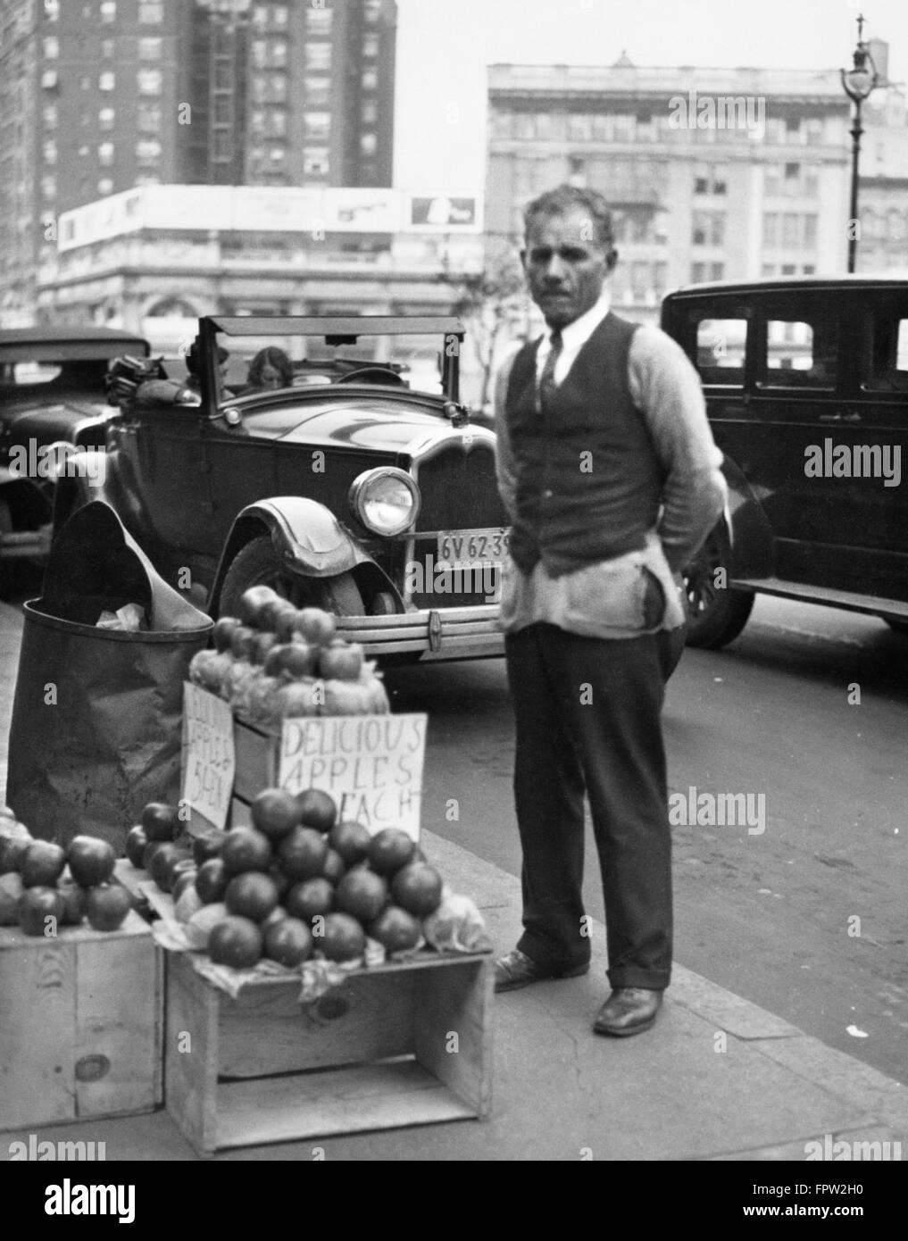 1930s SIDEWALK FORNITORE APPLE uomo guardando la fotocamera durante la Grande Depressione Immagini Stock