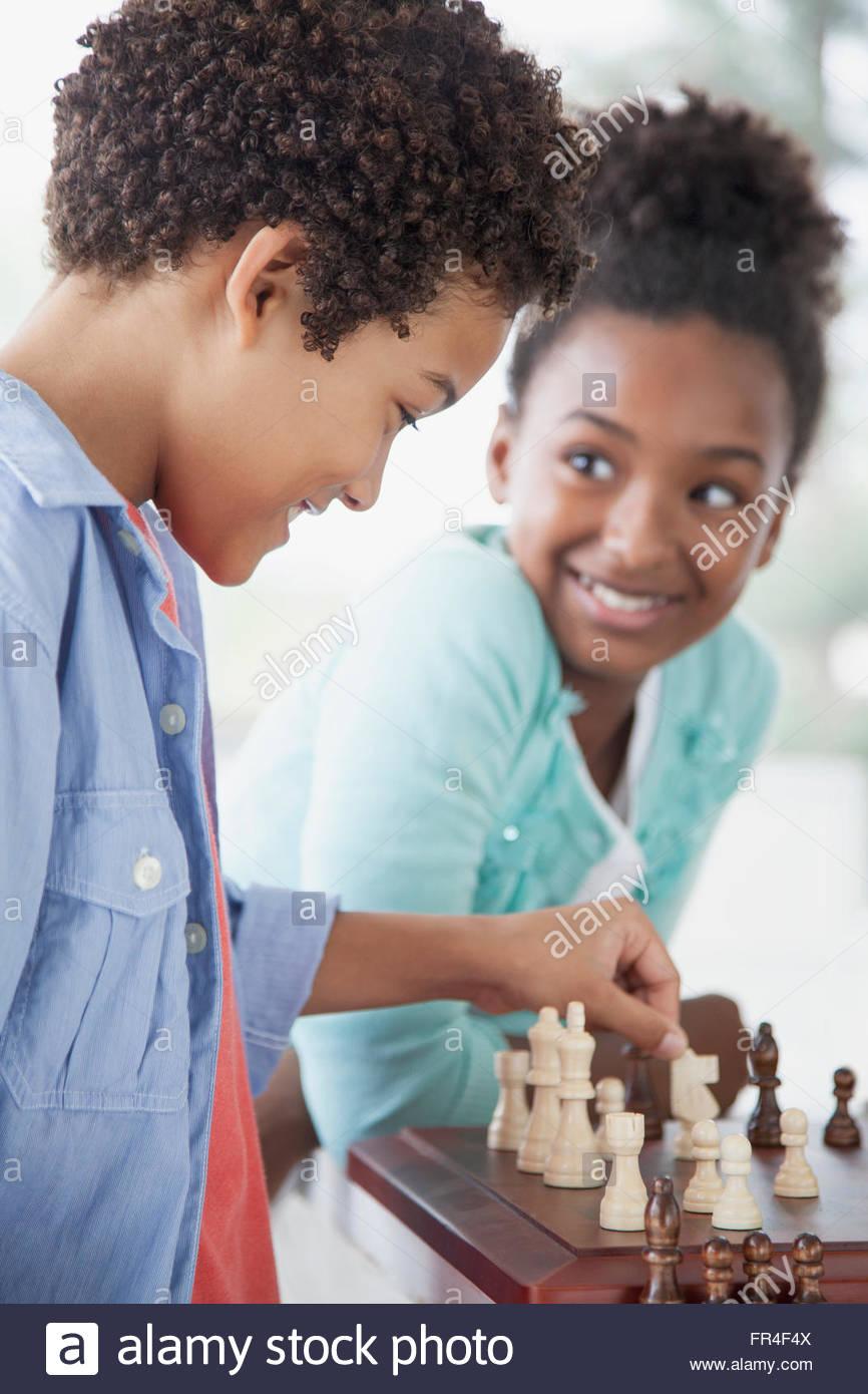 Suor guardando il fratello fare una mossa nel gioco degli scacchi Immagini Stock