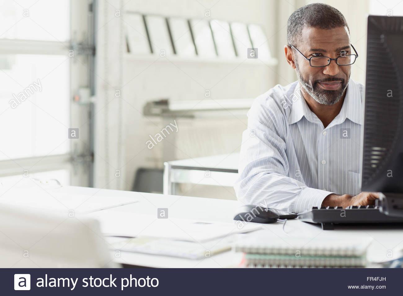 Imprenditore attraente al computer desktop Immagini Stock