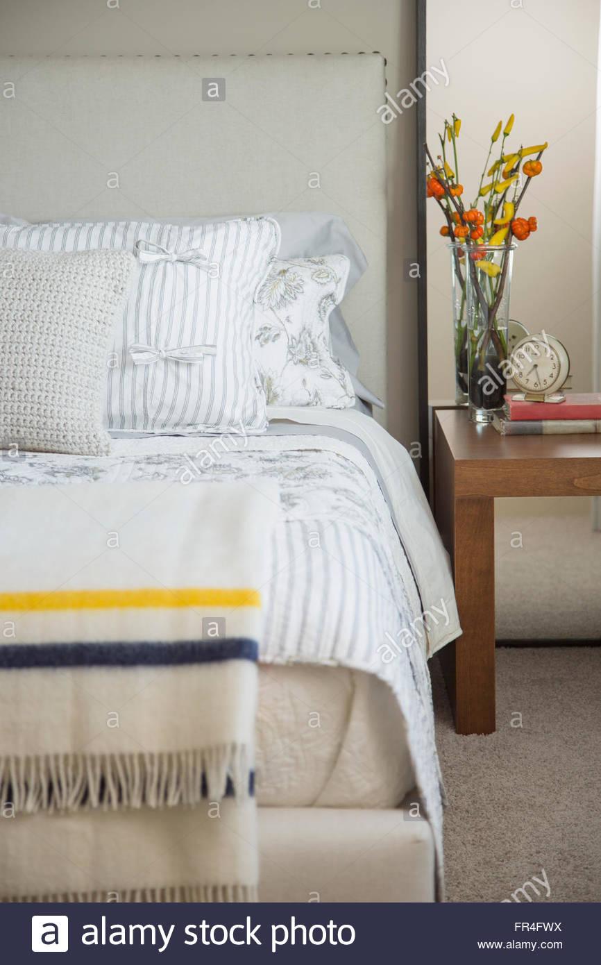 Close-up della camera da letto moderna con fiori sul comodino. Immagini Stock