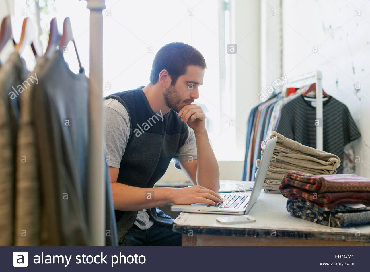 Giovani adulti addetto vendite lavorando sul computer portatile in mens usura store. Immagini Stock