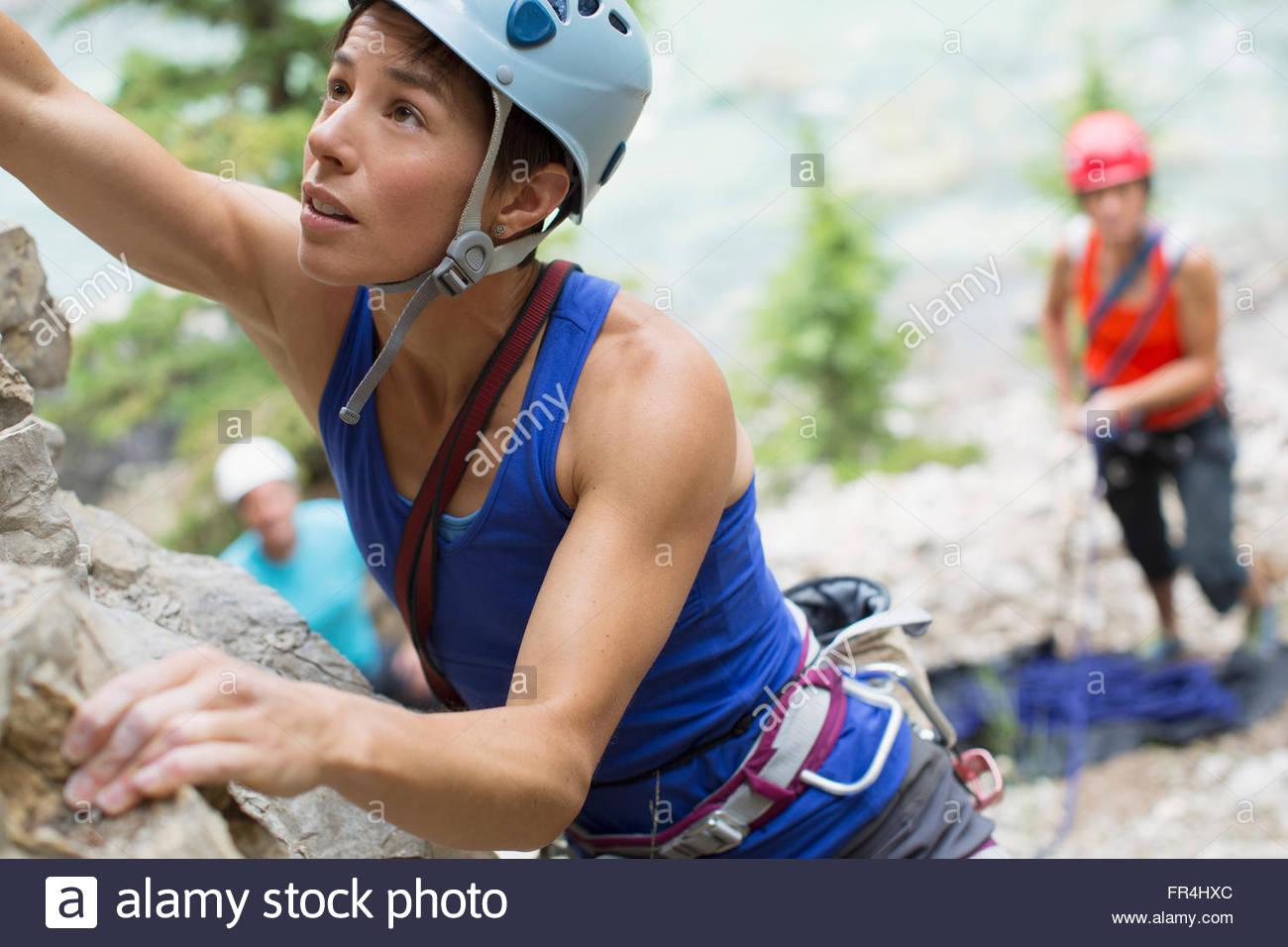 Arrampicatori guardando scalatore femmina andando su roccia Immagini Stock