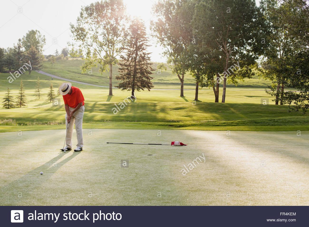 Senior uomo su di putt golf sul green Immagini Stock